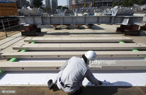 A Japan Sports Council member shows wood and steel frames to be used for the roof of the New National Stadium a venue for 2020 Summer Olympics and...
