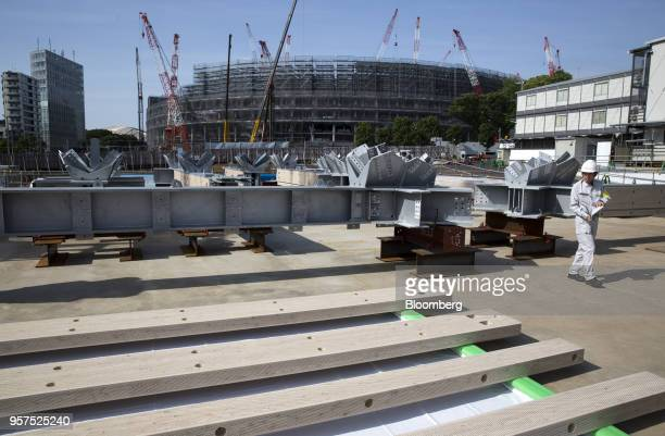 A Japan Sports Council member walks next to wood frames to be used for the roof of the New National Stadium a venue for 2020 Summer Olympics and...