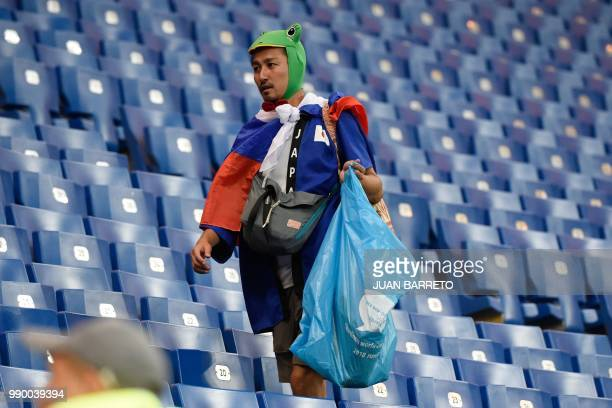 A Japan supporter collects rubbish after the Russia 2018 World Cup round of 16 football match between Belgium and Japan at the Rostov Arena in...