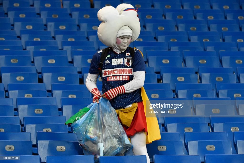 Japan supporter collects rubbish after the Russia 2018 World Cup round of 16 football match between Belgium and Japan at the Rostov Arena in Rostov-On-Don on July 2, 2018. (Photo by JUAN BARRETO / AFP) / RESTRICTED