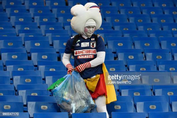 Japan supporter collects rubbish after the Russia 2018 World Cup round of 16 football match between Belgium and Japan at the Rostov Arena in...