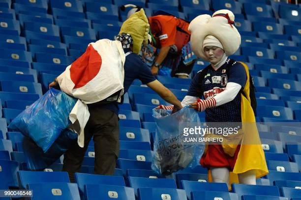 Japan supporters collect rubbish after the Russia 2018 World Cup round of 16 football match between Belgium and Japan at the Rostov Arena in...