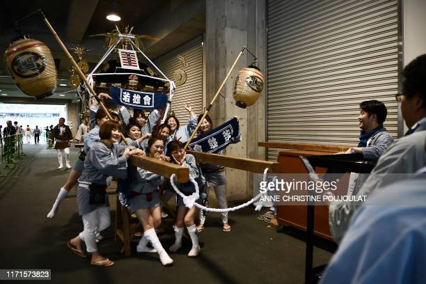 TOPSHOT Japan supporters pose with a mikoshi or portable shrine on display prior to the Japan 2019 Rugby World Cup Pool A match between Japan and...
