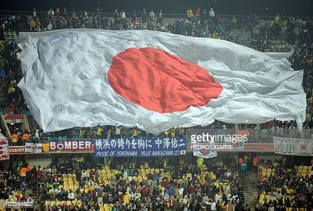 Japan supporters wave a giant flag as they cheer prior to the start of the Group E first round 2010 World Cup football match Denmark vs Japan on June...