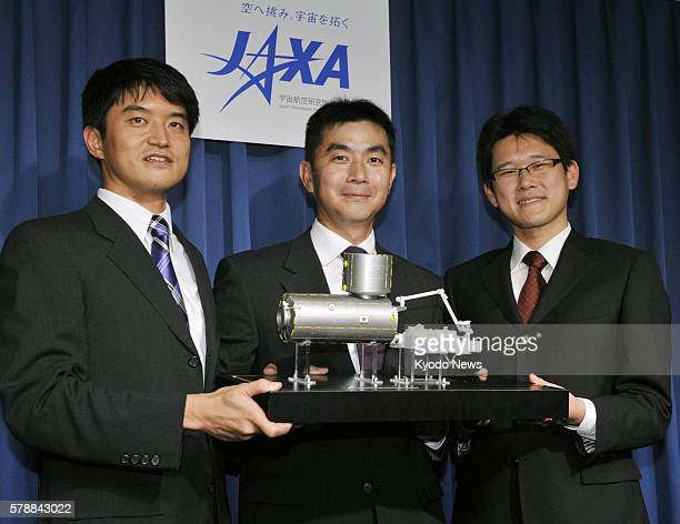 TOKYO Japan Takuya Onishi Kimiya Yui and Norishige Kanai hold a model of the International Space Station during a press conference in Tokyo on July...