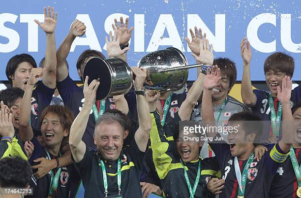 Japan team head coach Alberto Zaccheroni and players celebrate with the trophy after winning the EAFF East Asian Cup 2013 against South Korea at...