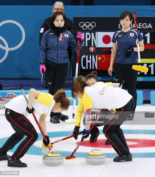 Japan team members look on in the ninth end of a women's curling roundrobin session match against China at the Pyeongchang Winter Olympics in...