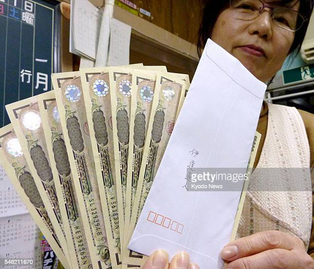YAMAGATA Japan The head of a nursery in Yamagata city northeastern Japan shows 100000 yen and an envelope on Jan 11 which the nursery received from...
