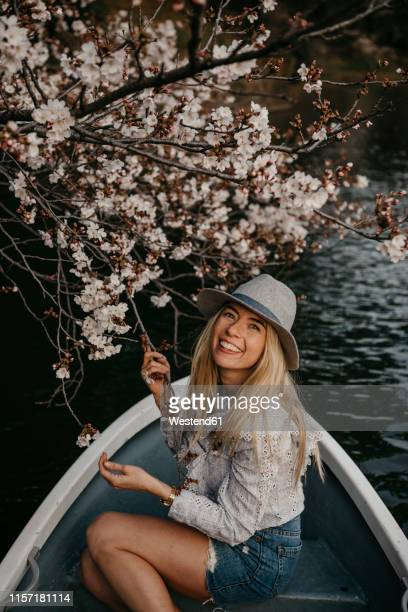 japan, tokio, chidorigafuchi park, smiling woman in rowing boat at cherry tree blossom - twig stock pictures, royalty-free photos & images