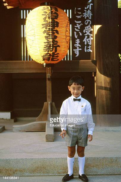 Japan Tokyo Boy Wearing Bow Tie And Shorts Standing In Front Of Traditional Lantern And Banner