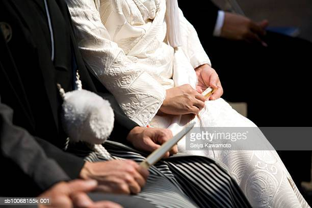 Japan, Tokyo, bride and groom sitting at ceremony, mid section, close up