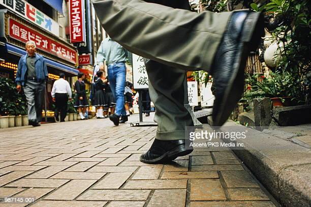 Japan, Tokyo, businessman walking along street, ground view