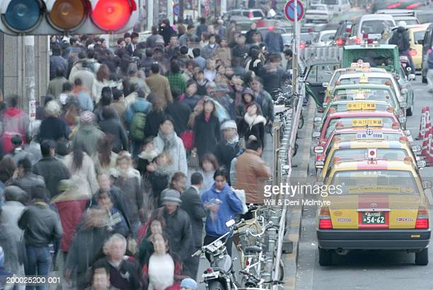 Japan, Tokyo, bustling sidewalk with cabs lined up at curb