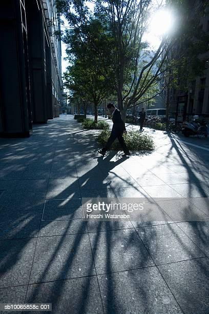 Japan, Tokyo, Chiyoda-ku, Marunouchi, businessman walking across street covered by sunlight