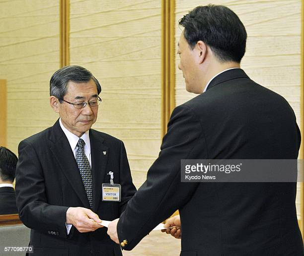TOKYO Japan Tokyo Electric Power Co President Masataka Shimizu hands a letter of request to industry minister Banri Kaieda at the prime minister's...