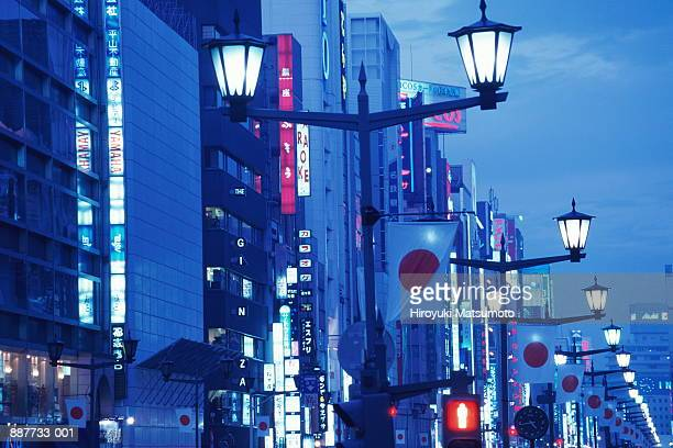 Japan, Tokyo, Ginza, Japanese flags hanging from lampposts, dusk