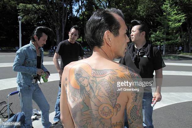 Japan Tokyo Harajuku Yoyogi Koen Park Asian man tattoo bare back cosplay costume play greaser Elvis motorcycle gang style hair