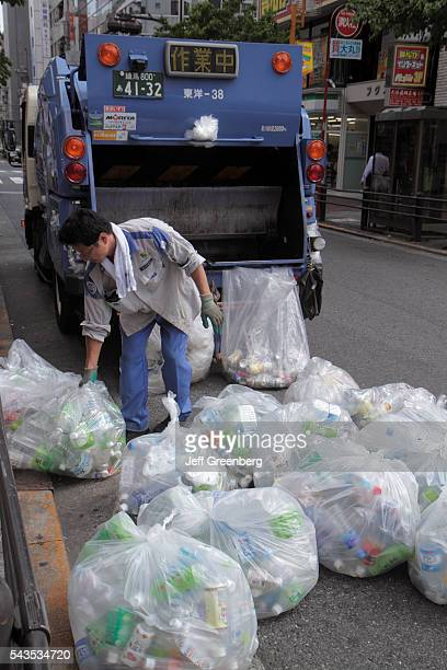 Japan Tokyo Ikebukuro garbage collection collector Asian man truck compactor plastic bags empty bottles recycling