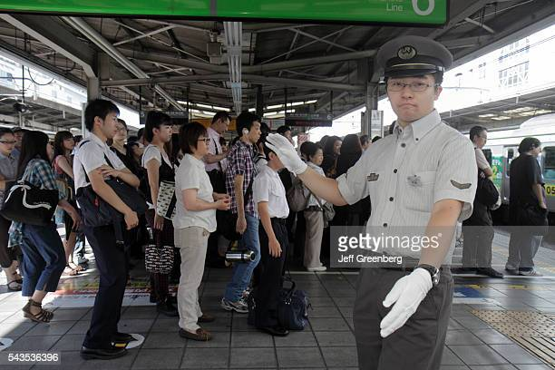 Japan Tokyo Ikebukuro JR Ikebukuro Station Yamanote Line platform attendant commuters line up lines queue rush hour