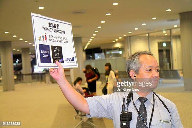 Japan Tokyo Narita International Airport NRT gate area concourse ANA Al Nippon Airways Asian man uniform holding sign priority boarding