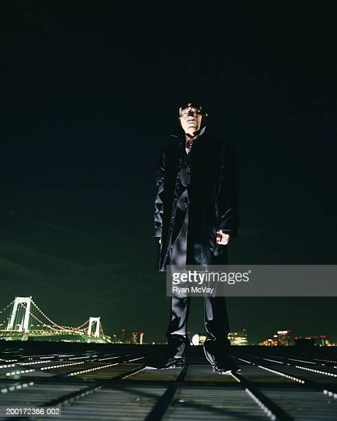 Japan, Tokyo, Odaiba, young businessman standing on rooftop, night