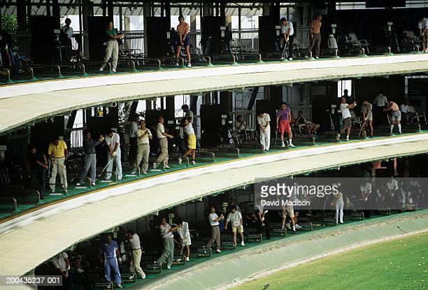 Japan, Tokyo, people at three-tiered driving range