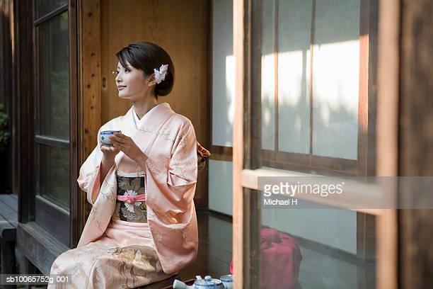 japan, tokyo, woman in kimono drinking tea - kimono stock pictures, royalty-free photos & images