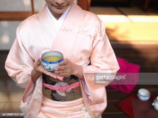 Japan, Tokyo, woman in kimono holding cup of green tea, mid section
