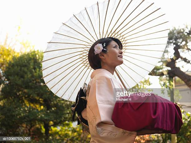 Japan, Tokyo, woman in kimono holding packaged gift and white umbrella