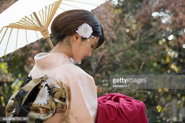 Japan, Tokyo, woman in kimono with white umbrella, looking down