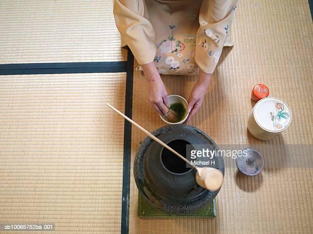 Japan, Tokyo, woman kneeling on floor, mixing green tea