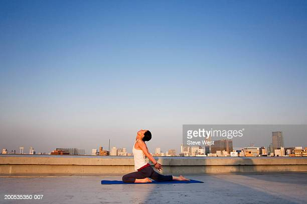 Japan, Tokyo, woman practicing yoga on rooftop at dusk, side view