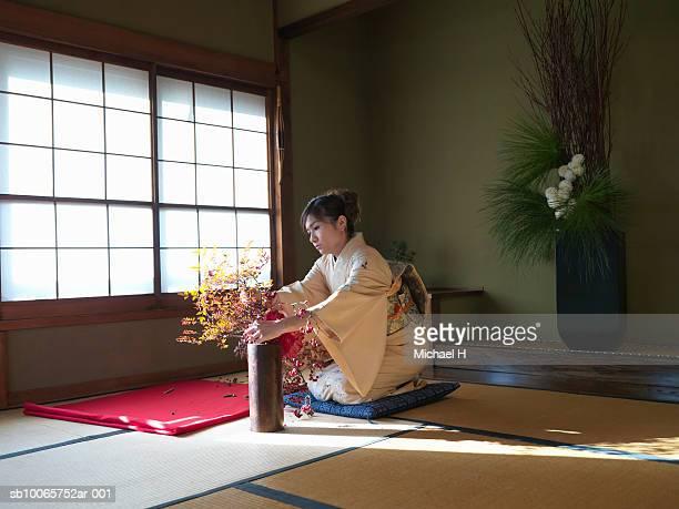 Japan, Tokyo, woman wearing kimono arranging flowers
