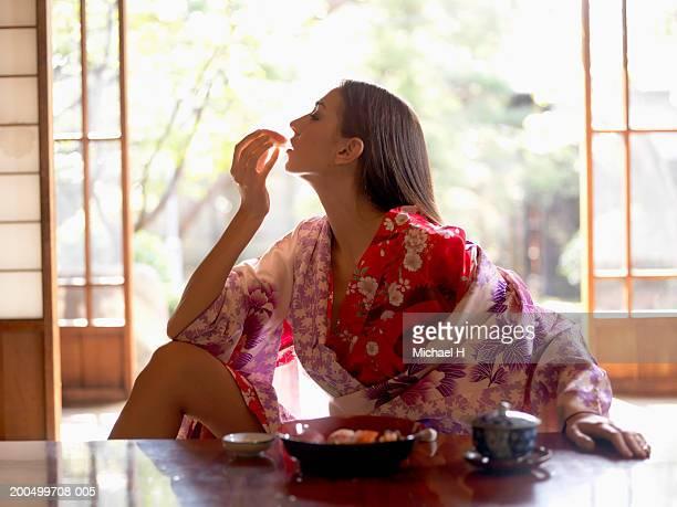 Japan, Tokyo, young woman in kimono eating sushi, side view