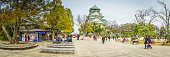 Japan tourists walking in the parkland around Osaka Castle panorama