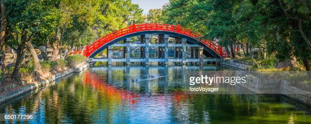 Japan traditional wooden arch bridge over tranquil river panorama Osaka
