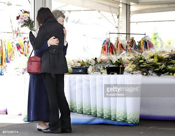 AMAGASAKI Japan Women hug each other in front of flowers offered at the site of a 2005 derailment of a West Japan Railway Co train on the Fukuchiyama...