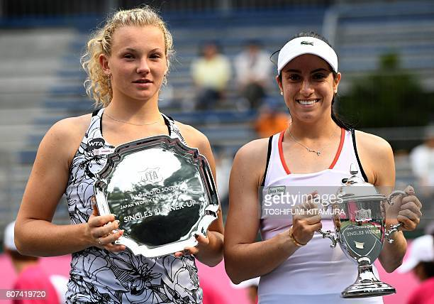 Japan Women's Open tennis singles winner Christina McHale of the US poses while holding her trophy beside runnerup Katerina Siniakova of Czech...
