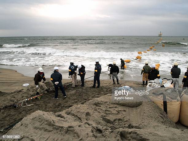 Japan - Workers pull an undersea fiber-optic cable from a ship anchored offshore to a beach in Minamiboso, Chiba Prefecture, on Nov. 19 as KDDI Corp....