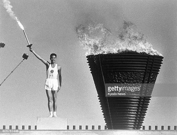 TOKYO Japan Yoshinori Sakai the final runner in the torch relay lights the Olympic cauldron during the opening ceremony of the Tokyo Olympics on Oct...