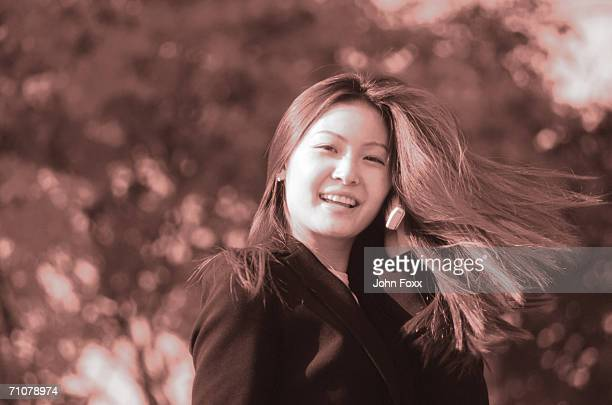 Japan, Young woman with hand in hair, smiling, portrait (B&W)