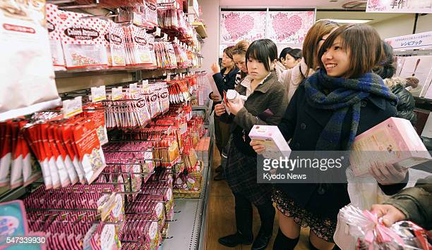 TOKYO Japan Young women choose decorative items for Valentine's Day chocolates at a store in Musashino Tokyo on Feb 13 the eve of the giftgiving day...