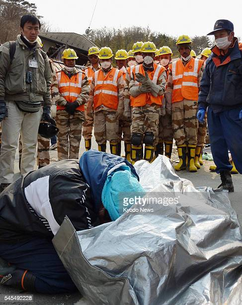 ONAGAWA Japan Yukiyoshi Sato cries in front of the recovered body of his mother as members of India's rescue team and others look on in the town of...