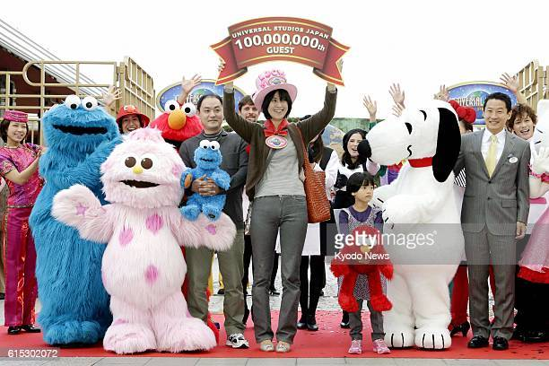 OSAKA Japan Yumiko Yamashita from Tokyo holds a number plate at Universal Studios Japan in Osaka on Oct 29 upon becoming the 100 millionth visitor to...