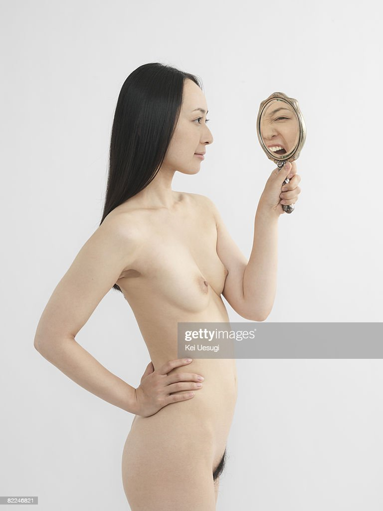 Japanaese woman looking into mirror, nude : Stock Photo