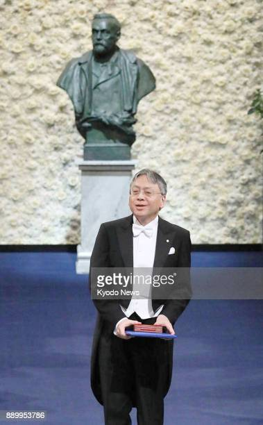 Japanborn British novelist Kazuo Ishiguro holds the 2017 Nobel Prize in literature medal and diploma after receiving them from Sweden's King Carl XVI...