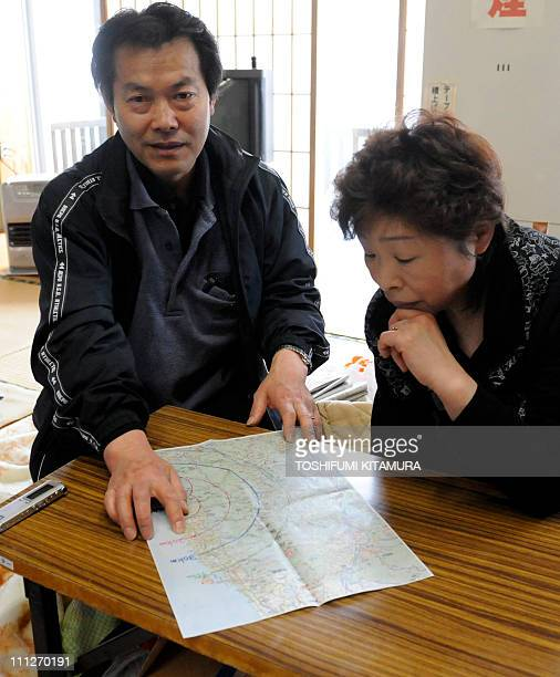 STORY JapandisasternuclearrefugeeFOCUS by Shingo ItoThis picture taken on March 28 2011 shows Toshinori Sato and his wife Tomoko pointing to their...