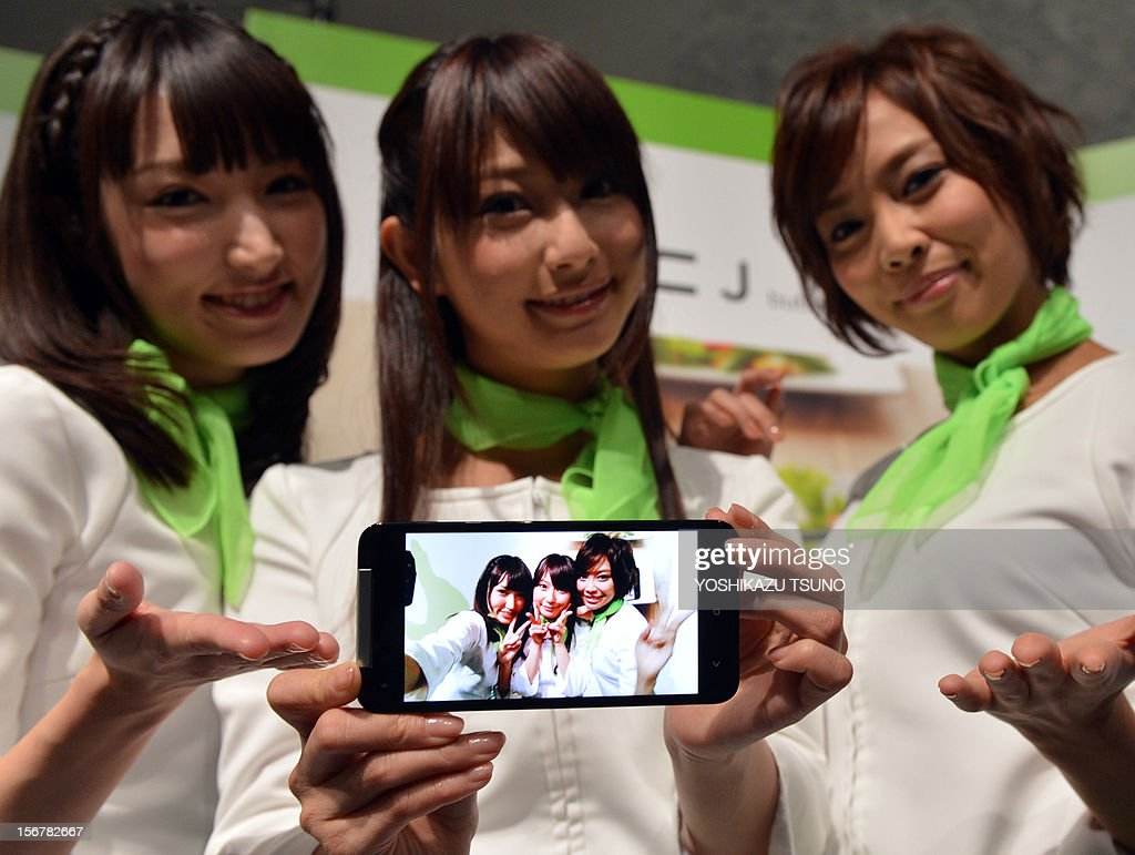 Japan-electronics-technology-camera,FOCUS by Hiroshi Hiyama This photo taken on November 20, 2012 shows models displaying a self-portrait taken with a new 8 mega-pixel camera/smartphone called the 'HTCJ butterfly', produced by Taiwanese electronics maker HTC, in Tokyo. The soaring popularity of smartphones is crushing demand for point-and-shoot cameras, threatening the once-vibrant sector's survival as firms scramble to shift their strategy, analysts say. AFP PHOTO / Yoshikazu TSUNO