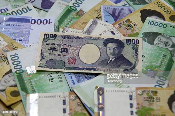 A Japanese 1000 yen banknote sits on a pile of South Korean won banknotes for an arranged photograph at a Woori Bank Co branch in Seoul South Korea...