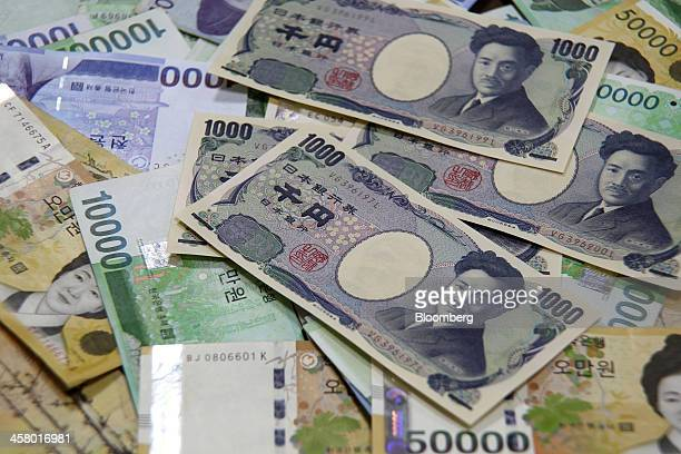 Japanese 1000 yen banknotes and South Korean won banknotes are arranged for a photograph at a Woori Bank Co branch in Seoul South Korea on Thursday...